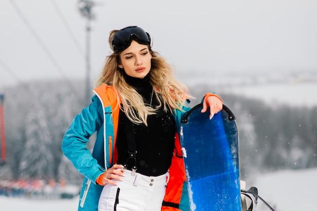 Młoda sportowa uśmiechnięta kobieta zimą z snowboard