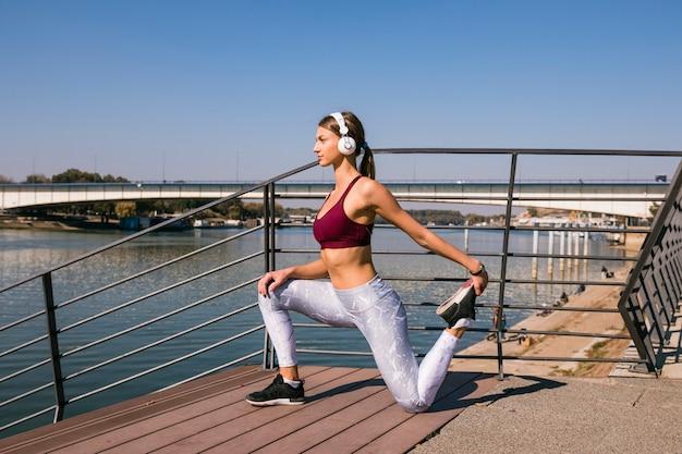 Młoda sportowa żeńska słuchająca muzyka na hełmofonie rozciąga jej nogę na moscie