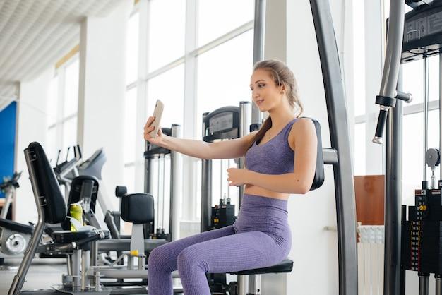 Młoda sportowiec korzysta z telefonu na siłowni i robi sobie selfie.