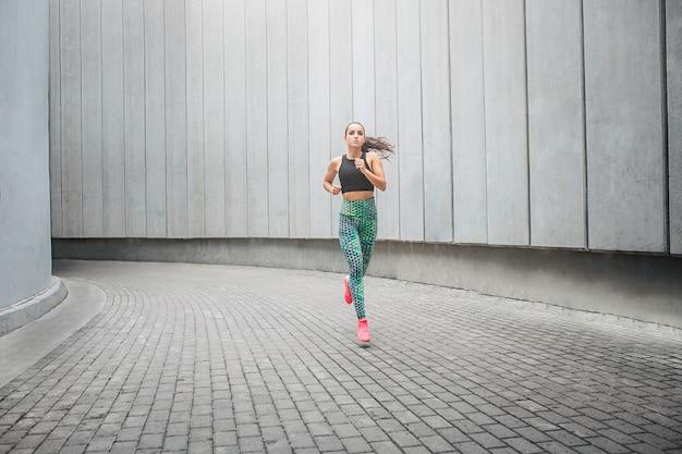 Młoda sportsmenka biegnąca w korytarzu