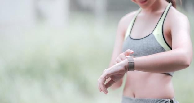 Młoda sportsmenka dotyka ekranu smartwatcha w aktywnej aktywności sportowej. skopiuj miejsce.