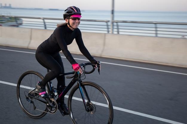 Młoda sportsmenka jedzie na rowerze i uśmiecha się
