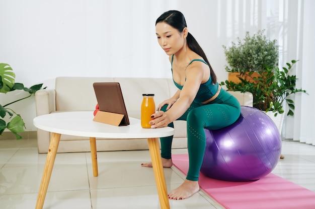 Młoda sportsmenka pije sok z marchwi między seriami podczas ćwiczeń w domu