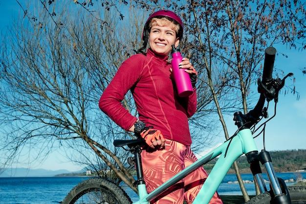 Młoda sportsmenka pije wodę, żeby się odświeżyć