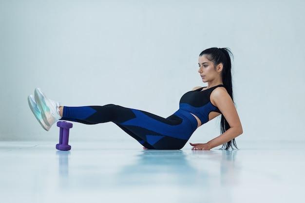 Młoda sportsmenka potrząsa prasą lekkoatletyczna dziewczyna sprawia, że ćwiczenia fitness leżą na podłodze