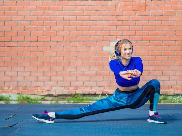 Młoda sportsmenka rozciąga się i przygotowuje się do uruchomienia. pojęcie zdrowego stylu życia.