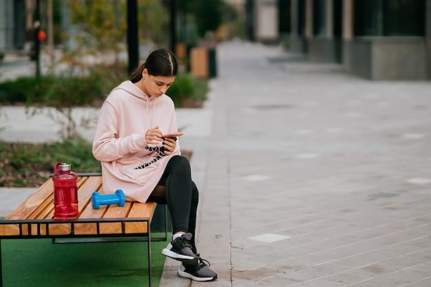Młoda sportsmenka siedząca na ławce w parku