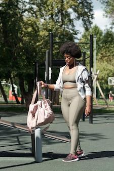 Młoda sportsmenka umieszcza swoją torbę na obiektach sportowych