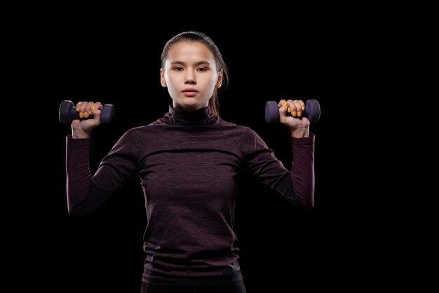 Młoda sportsmenka w odzieży sportowej, patrząc na ciebie podczas ćwiczeń z hantlami na czarnej ścianie w izolacji
