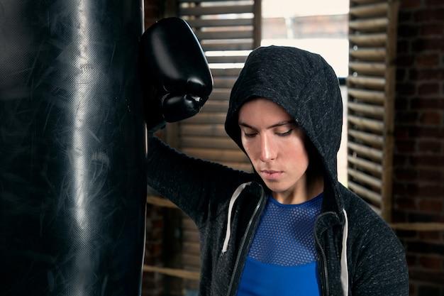 Młoda sportsmenka w rękawicach bokserskich w pobliżu worka treningowego