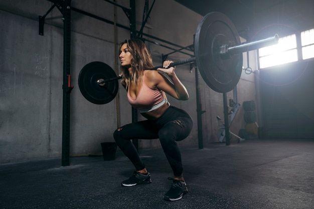 Młoda sportsmenka ze sztangą napinającą mięśnie i kucającą na ramieniu.