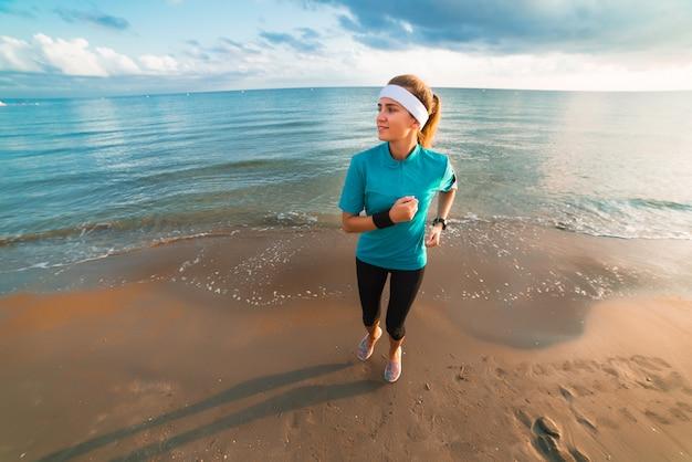 Młoda sporty dziewczyna biega na plaży przy wschodem słońca w ranku