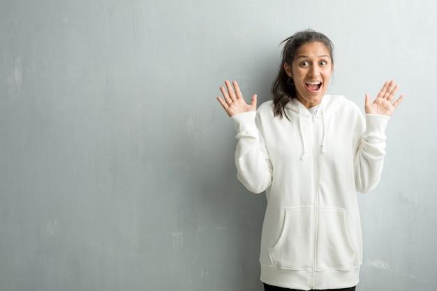 Młoda sporty indyjska kobieta przeciw gym ścianie krzyczy szczęśliwy, zaskakujący ofertą lub ap
