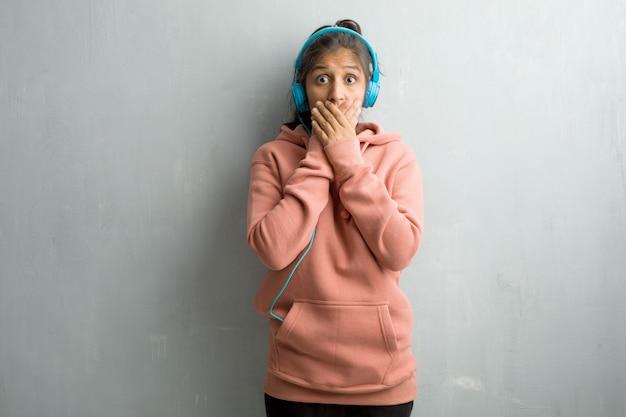 Młoda sporty indyjska kobieta przeciw ściennemu nakryciu usta, symbolowi cisza i represja