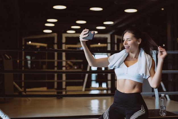 Młoda sporty kobieta bierze selfie z telefonem komórkowym przy gym.