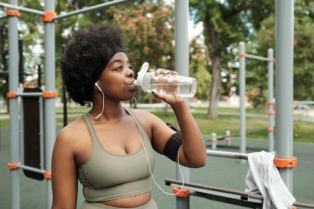 Młoda spragniona kobieta w dresie pije wodę z plastikowej butelki