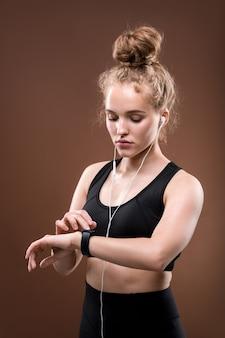 Młoda sprawna aktywna kobieta w czarnej odzieży sportowej i słuchawkach patrząc na zegarek przed rozpoczęciem ćwiczeń lub joggingu