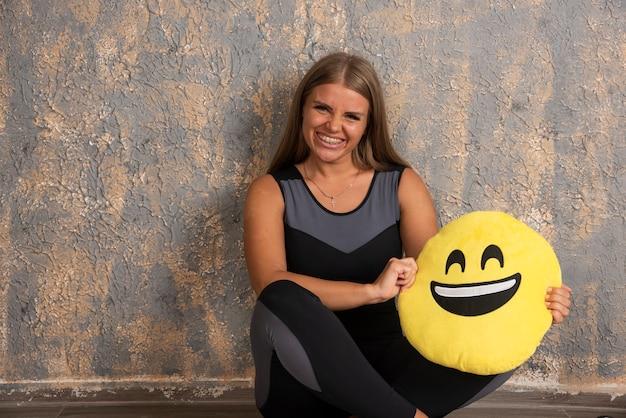 Młoda sprawna dziewczyna w sportowych strojach trzyma poduszkę z uśmiechem emoji poniżej.