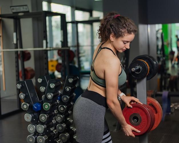 Młoda sprawna kobieta bierze krążek ze sztangą ze stojaka na siłowni. wolny trening siłowy