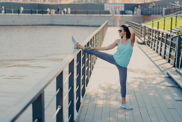 Młoda, sprawna kobieta o ciemnych włosach rozciąga nogi na płocie rozgrzewa się przed bieganiem, nosi okulary przeciwsłoneczne, t-shirt, legginsy i trampki, przygotowuje się do treningu cardio pozy będąc w dobrej formie fizycznej