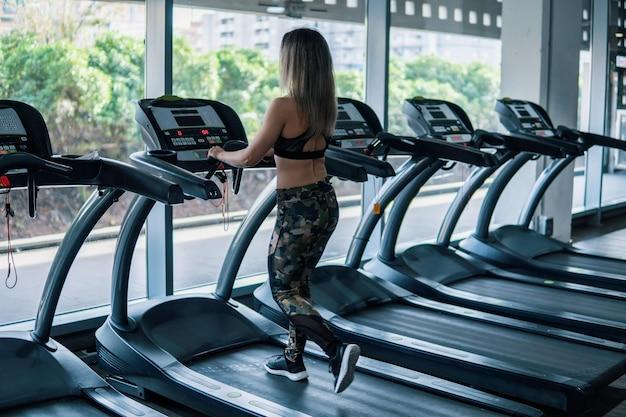 Młoda sprawna kobieta robi bieganie ćwiczenia w siłowni na bieżni speedwalk systemem drogi.