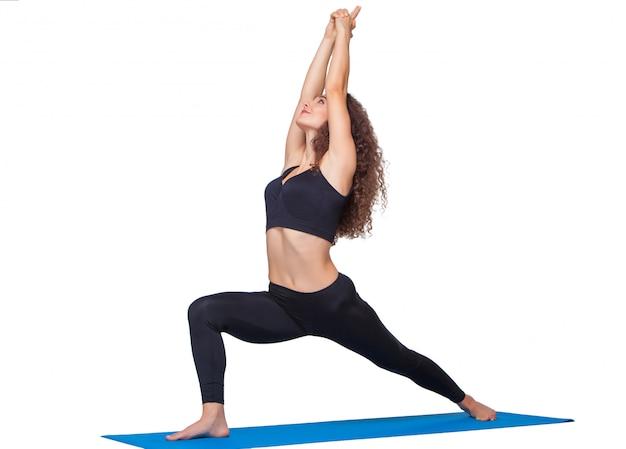 Młoda sprawna kobieta robi ćwiczenia jogi.