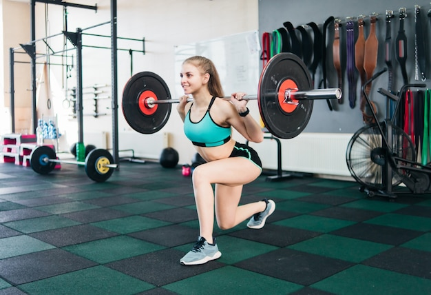 Młoda sprawna kobieta rzuca nogi ze sztangą na ramionach na siłowni