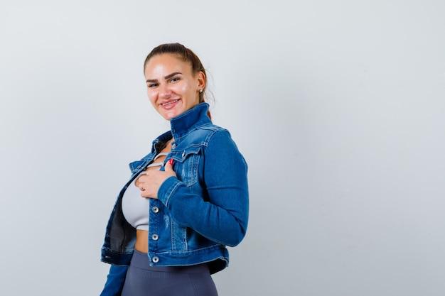 Młoda sprawna kobieta w górnej, dżinsowej kurtce trzymając rękę na klatce piersiowej podczas pozowanie i patrząc wesoło, widok z przodu.