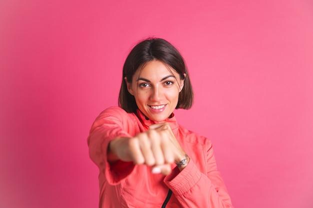 Młoda sprawna kobieta w sportowej kurtce na różowo robi gest walki