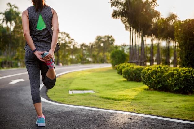 Młoda sprawności fizycznej kobieta ćwiczy w pogodnym jaskrawym świetle w ranku przed biegać.
