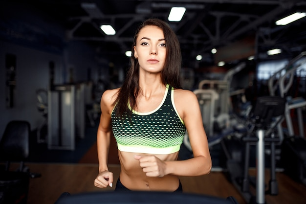 Młoda sprawności fizycznej kobieta robi cardio ćwiczeniom przy gym biega na karuzeli.