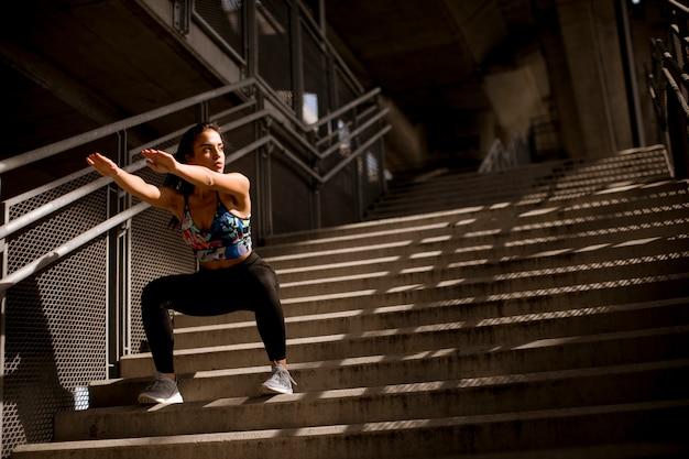 Młoda sprawności fizycznej kobieta robi ćwiczeniom plenerowym