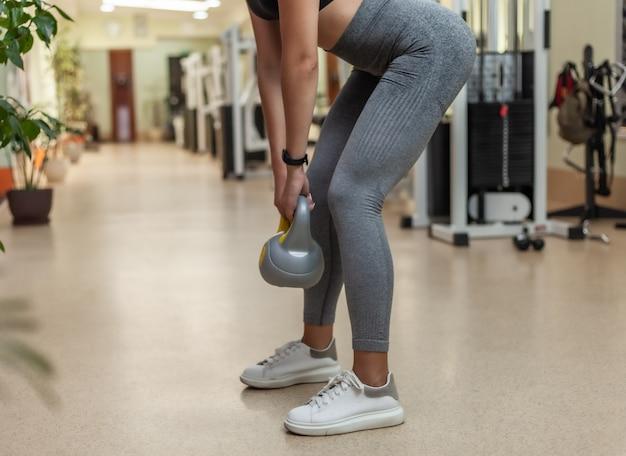 Młoda sprawności fizycznej kobieta robi ćwiczeniu z kettlebell w gym. trening funkcjonalny z wolnymi ciężarami. przyciąć zdjęcie