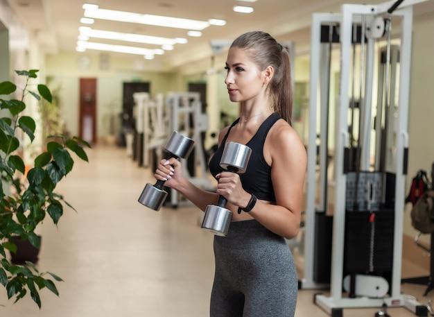 Młoda sprawności fizycznej kobieta robi podnośnemu ćwiczeniu z dumbbells w jej ręce przy gym. trening funkcjonalny z wolnymi ciężarami
