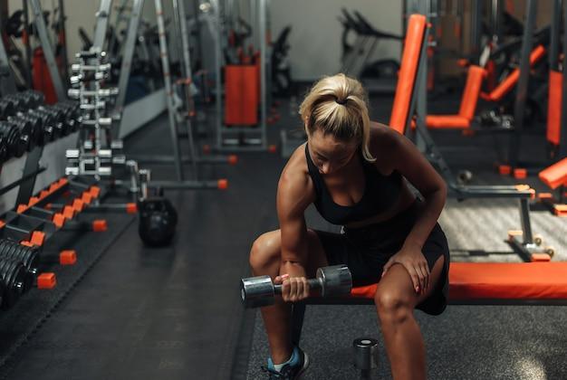 Młoda sprawności fizycznej kobieta robi skoncentrowanemu robi dumbbell podnosi dla bicepsa jeden ręki podczas gdy siedzący na ławce w gym. koncepcja treningowa z wolnymi ciężarami.