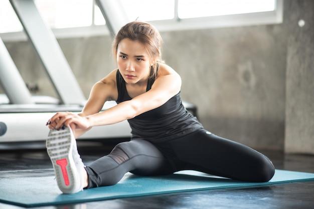Młoda sprawności fizycznej kobieta rozciąga jej nogę ogrzewać przy gym