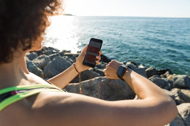 Młoda sprawności fizycznej kobieta tworzy jej smartwatch