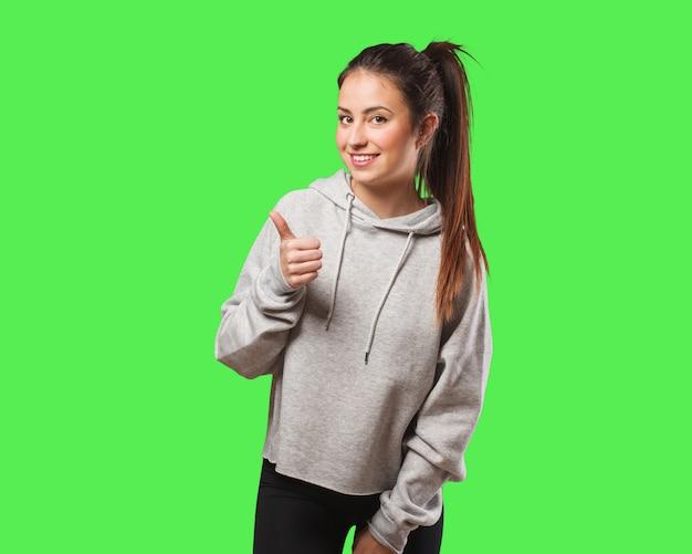 Młoda sprawności fizycznej kobieta uśmiecha się kciuk up i podnosi