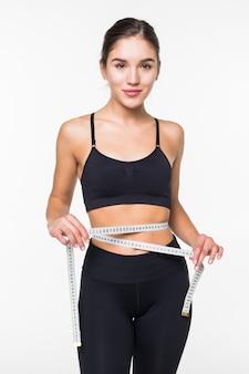 Młoda sprawności fizycznej kobiety miara z taśmą jej brzuch odizolowywający na biel ścianie