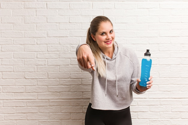 Młoda sprawności fizycznej rosyjska kobieta trzyma napój energetycznego