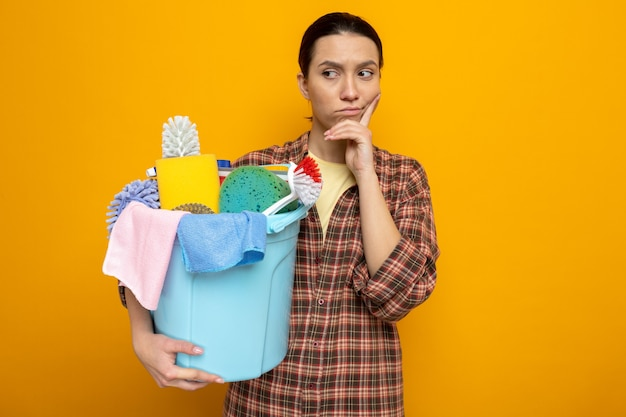 Młoda sprzątaczka w koszuli w kratę, trzymająca wiadro z narzędziami do czyszczenia, patrząc na bok z zamyślonym wyrazem twarzy, myśląc stojąc na pomarańczowo