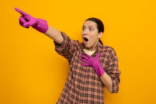 Młoda sprzątaczka w koszuli w kratę w gumowych rękawiczkach, patrząc na bok zdumiona i zdziwiona, wskazując palcem wskazującym na coś stojącego nad pomarańczową ścianą