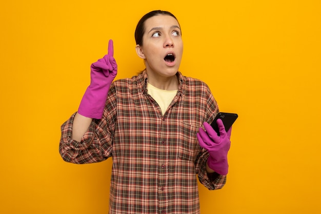 Młoda sprzątaczka w koszuli w kratę w gumowych rękawiczkach, trzymając smartfona patrząc w górę zaskoczony pokazując palec wskazujący mający nowy pomysł