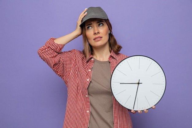 Młoda sprzątaczka w kraciastej koszuli i czapce, trzymająca zegar patrząc w górę zmieszana z ręką na głowie
