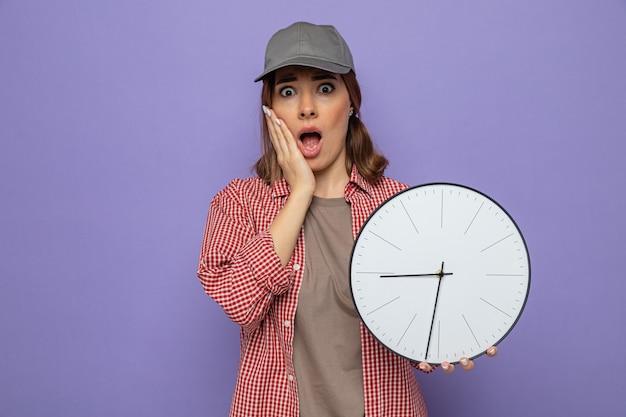 Młoda sprzątaczka w kraciastej koszuli i czapce, trzymająca zegar, wyglądająca na zszokowaną