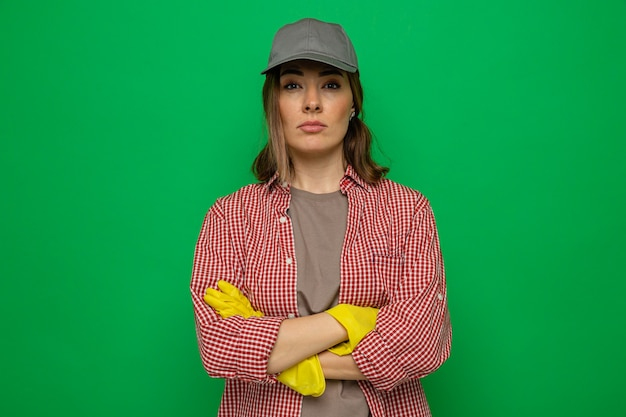 Młoda sprzątaczka w kraciastej koszuli i czapce w gumowych rękawiczkach, patrząca na kamerę z poważną twarzą ze skrzyżowanymi rękami, stojącą na zielonym tle
