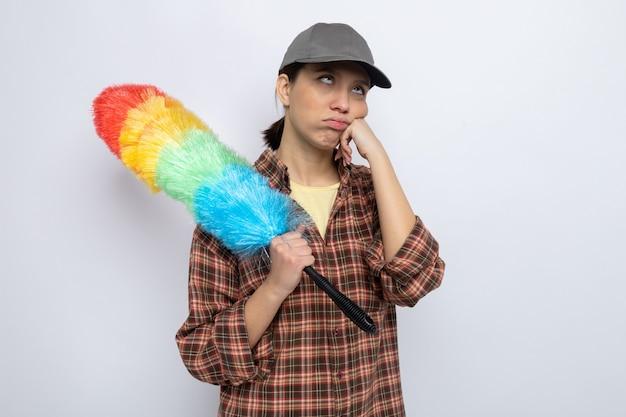 Młoda sprzątaczka w zwykłych ubraniach i czapce, trzymająca kolorową szczotkę do kurzu, wyglądająca na zmęczoną i wyczerpaną, przewracając oczami stojąc na białym tle