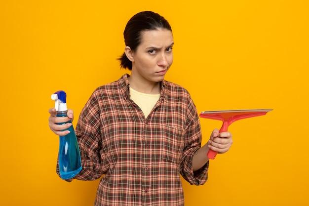 Młoda sprzątaczka w zwykłych ubraniach trzyma spray do czyszczenia i mop, patrząc z marszczącą twarz