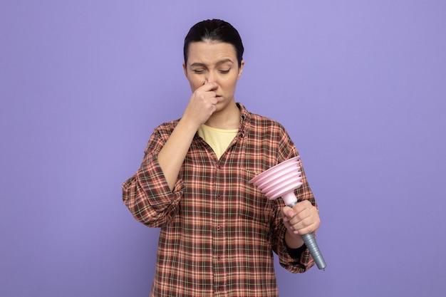 Młoda sprzątaczka w zwykłych ubraniach trzyma tłok, patrząc na niego, zamyka nos palcami cierpiący na smród stojący nad fioletową ścianą