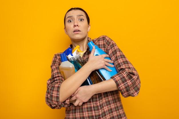 Młoda sprzątaczka w zwykłych ubraniach, trzymająca środki czystości, patrząca z przodu zmartwiona, stojąca nad pomarańczową ścianą